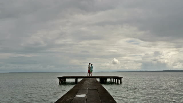 vídeos de stock e filmes b-roll de man and woman dancing on end of dock on ocean. - docas
