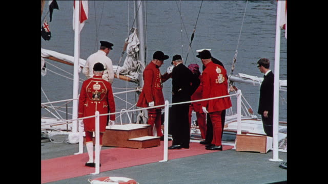 man and woman depart sailboat / royal footmen assist man and woman ashore / couple walk down red carpet / man kneels on platform / queen elizabeth... - documentary footage stock videos & royalty-free footage