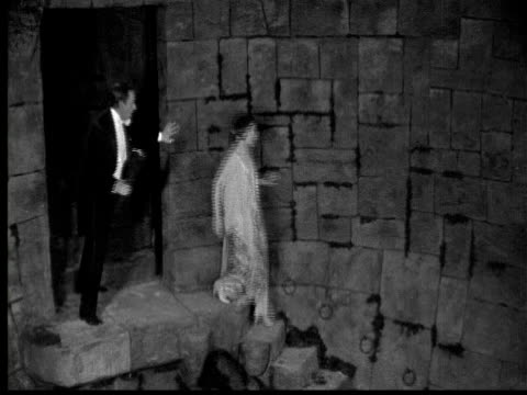 1925 ms b/w man and woman descending steps in dungeon - dungeon stock videos & royalty-free footage