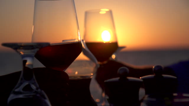 A man and woman dine and drink wine on a tropical island beach. - Slow Motion
