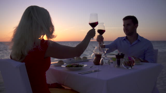 a man and woman dine and drink wine on a tropical island beach. - tropical drink stock videos & royalty-free footage