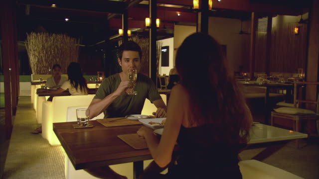 stockvideo's en b-roll-footage met ms man and woman dining in restaurant and toasting with wine / hua hin, thailand - gezicht aan gezicht