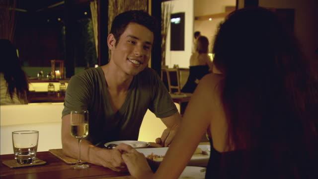 cu man and woman dining in restaurant, talking and holding hands / hua hin, thailand - 向かい合わせ点の映像素材/bロール