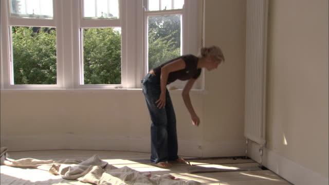 vídeos de stock e filmes b-roll de man and woman discovering problem underneath floorboards as they attempt diy project in empty room - pano de protecção