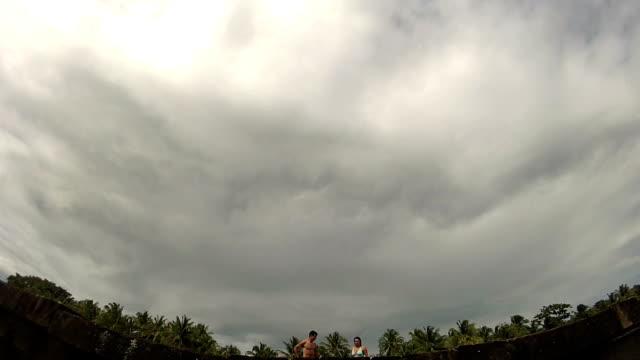 vídeos y material grabado en eventos de stock de pov of man and woman doing a high five jumping off end dock away from camera into tropical ocean. - bañador de natación