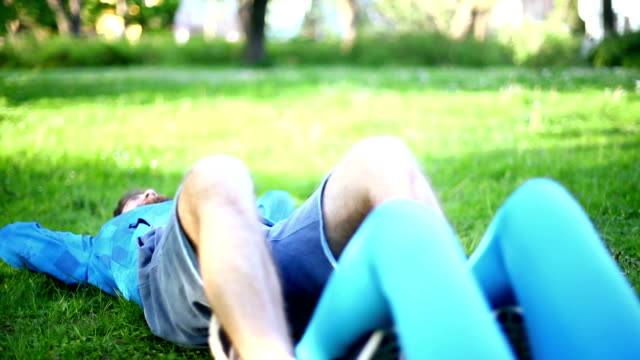 vídeos y material grabado en eventos de stock de hombre y mujer haciendo abs en un parque. - manos detrás de la cabeza