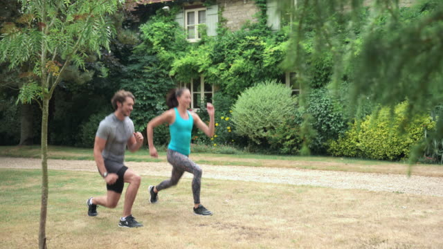 man and woman doing jumping lunges - lunge stock videos & royalty-free footage