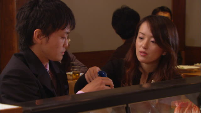 cu, man and woman drinking sake in bar - アルコール飲料点の映像素材/bロール