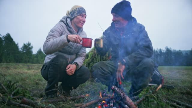 mann und frau trinken tee durch das feuer, das sie auf der waldlichtung entzündet - überleben stock-videos und b-roll-filmmaterial