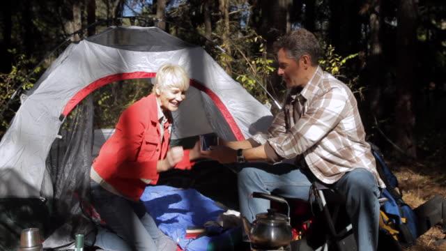 ms man and woman drinking tea near tent in forest / clinton, new jersey, usa - teekessel stock-videos und b-roll-filmmaterial