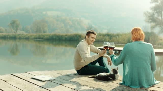 Mann und Frau Weintrinken am Pier von See