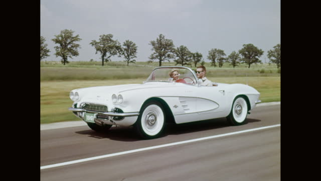 MS TS Man and woman driving 1959 Chevrolet Corvette convertible on road / United States