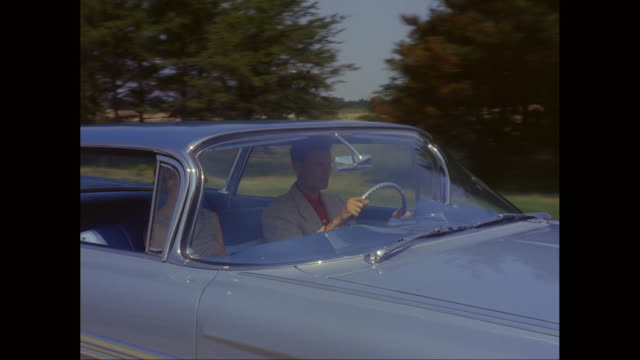 MS TS Man and woman driving 1959s Chevrolet car on road / United States