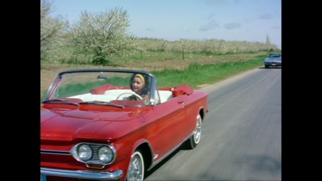 ws pov zi man and woman driving 1964 chevrolet car on street / united states - collector's car stock videos and b-roll footage
