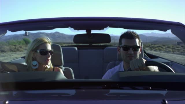 ms, man and woman driving convertible car through desert, near san diego, california, usa - man convertible stock videos & royalty-free footage