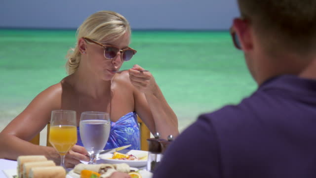 A man and woman eat breakfast on a tropical island beach.