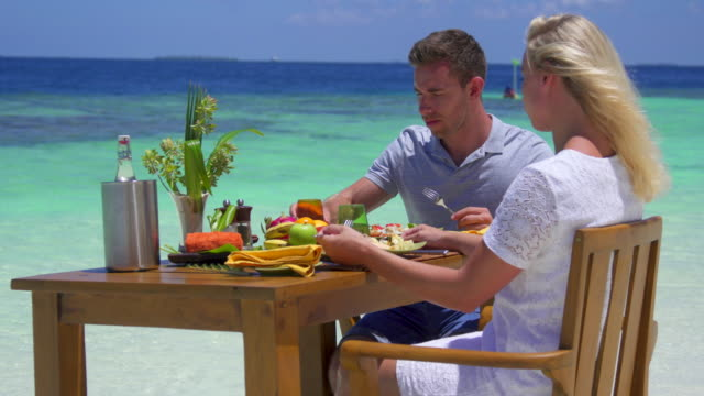 a man and woman eat breakfast on a tropical island beach. - essen mund benutzen stock-videos und b-roll-filmmaterial