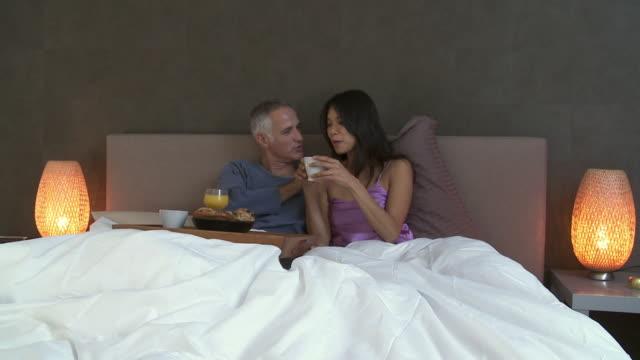 vídeos y material grabado en eventos de stock de ws man and woman eating breakfast and laughing in bed / brussels, belgium - bandeja para servir
