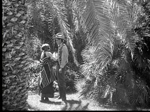 b/w 1920 ms man and woman embracing in garden - fächerpalme stock-videos und b-roll-filmmaterial