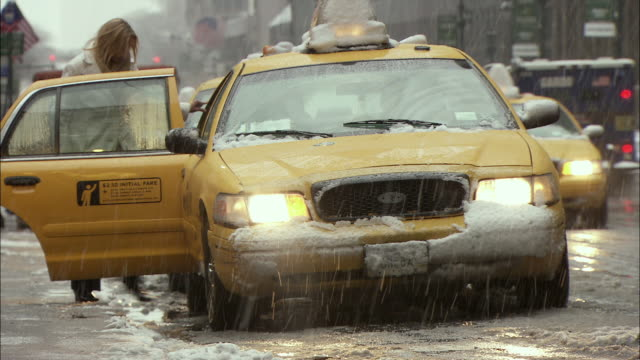 vidéos et rushes de ms man and woman entering yellow cab on snowy street / new york city, new york, usa - yellow taxi