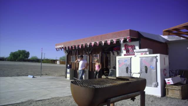 ws, man and woman exiting desert bar, near san diego, california, usa - san diego stock videos & royalty-free footage