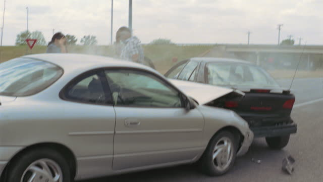 WS Man and woman exiting smoking cars after accident and looking at their damaged vehicles / Elmendorf, Texas, USA