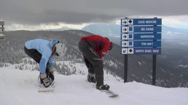 ws, man and woman fastening snowboards on ski slope, whitefish, montana, usa - ski slope stock videos & royalty-free footage
