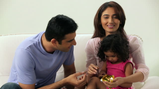 man and woman feeding chocolate to their daughter  - maharashtra stock-videos und b-roll-filmmaterial