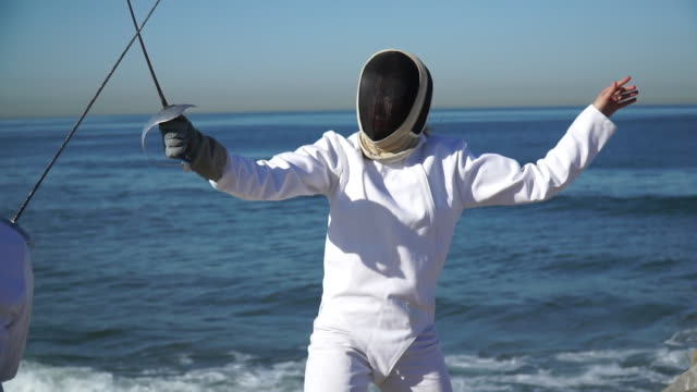vídeos y material grabado en eventos de stock de a man and woman fencing on the beach. - slow motion - tocado accesorio de cabeza