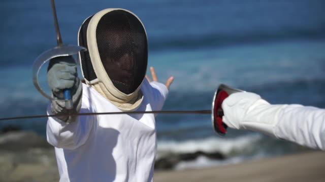 vídeos y material grabado en eventos de stock de a man and woman fencing on the beach. - slow motion - en guardia