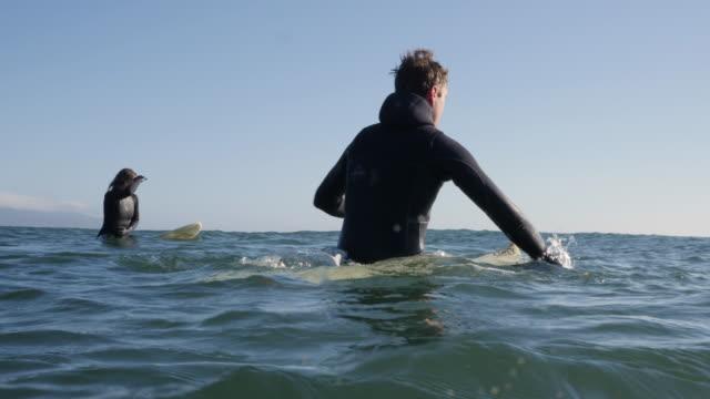 vídeos de stock, filmes e b-roll de homem e mulher flutuando nas pranchas de surf no oceano - diving suit