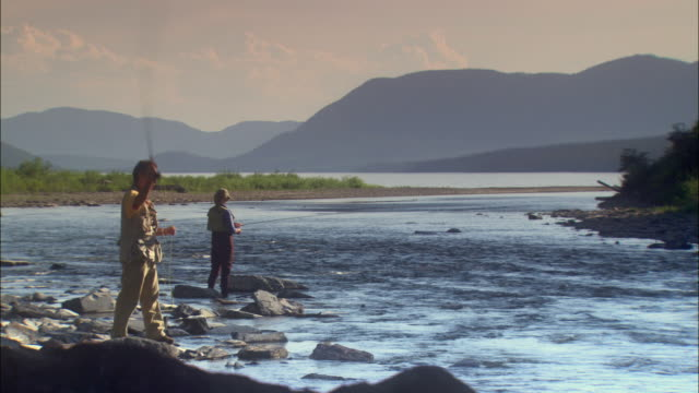 vidéos et rushes de ws man and woman fly fishing in rocky stream, mountains in background / glacier national park, montana, usa - montana