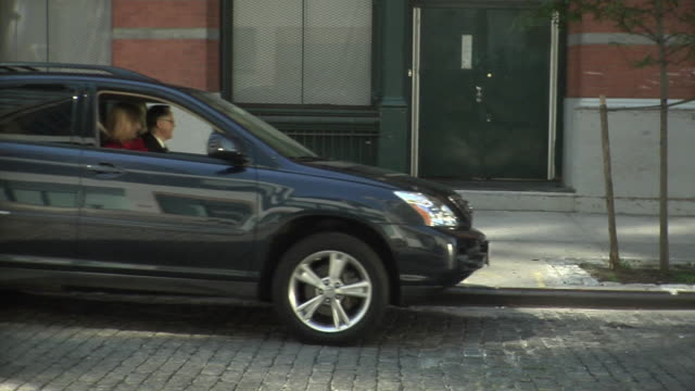 ws man and woman getting out of suv and walking away, tribeca, new york, usa - suv点の映像素材/bロール