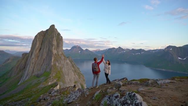 man and woman giving high five near  segla   mountain on senja island - north stock videos & royalty-free footage