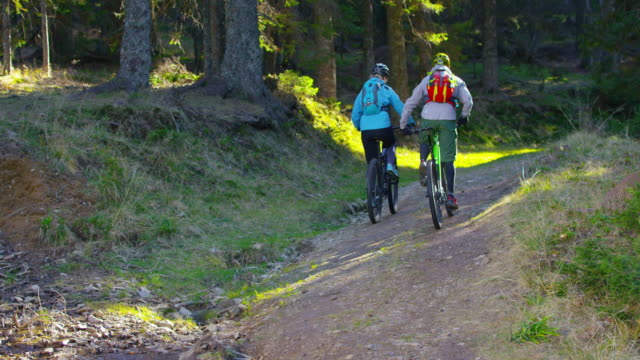 SLO MO Man and woman going uphill on mountain bikes