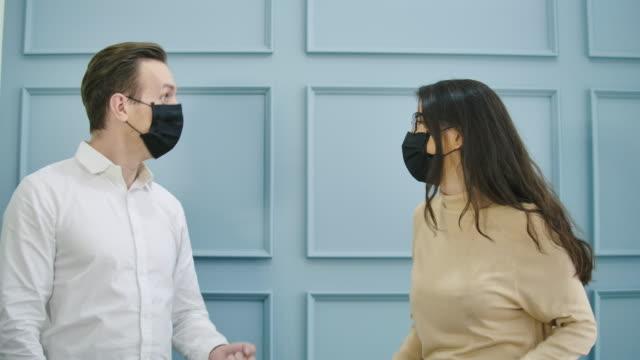 vídeos y material grabado en eventos de stock de hombre y mujer saludando el uno al otro con nuevo estilo de apretón de manos en la oficina. - codo