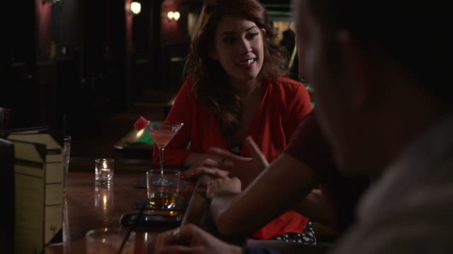 stockvideo's en b-roll-footage met man and woman having a conversation at a cocktail bar - martiniglas
