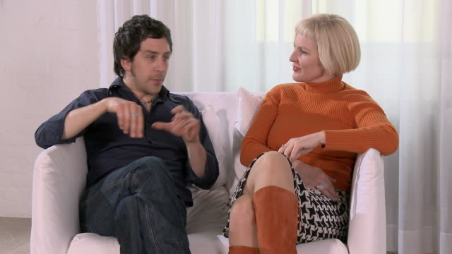 ms man and woman having an animated conversation on loveseat/ berlin, germany - polo neck stock videos & royalty-free footage