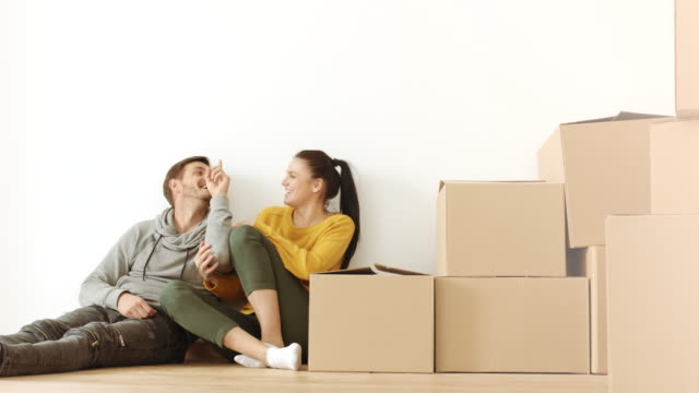 Man and woman having fun in room full of cardboard boxes