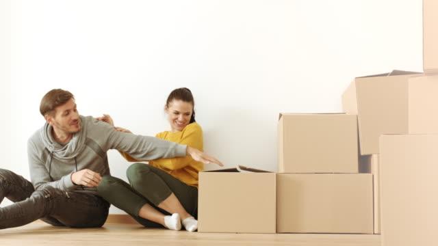 Man en vrouw plezier in kamer vol met kartonnen dozen