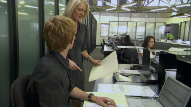 ms man and woman having meeting at table in office/ ts man at desk answering phone call/ sydney, australia - 電話を切る点の映像素材/bロール