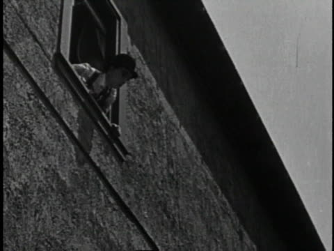 1920 MONTAGE Man and woman hide in room as villain batters the door, then woman jumps from window onto safety net held by police