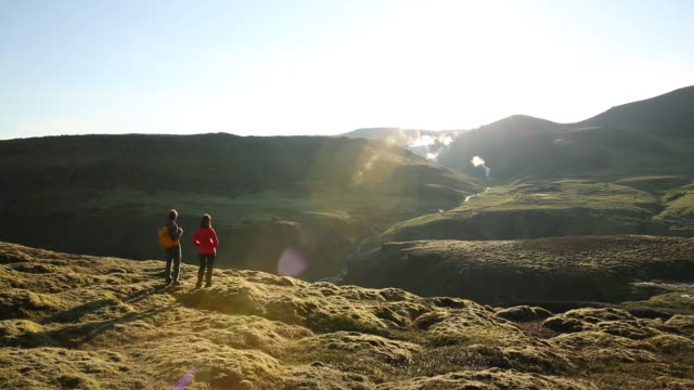 A man and woman hiking a beautiful trail in Iceland, with waterfalls and sun flare in the distance.
