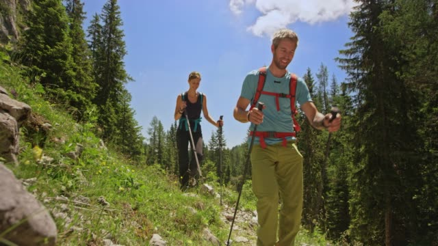man and woman hiking down a mountain in sunshine - hiking pole stock videos and b-roll footage