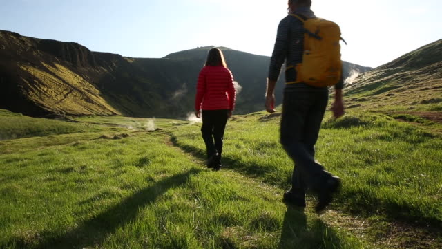 Man and woman hiking in a lush green field in Iceland