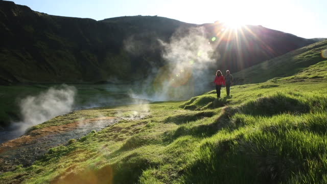 man and woman hiking in a lush green field in iceland - thermalquelle stock-videos und b-roll-filmmaterial