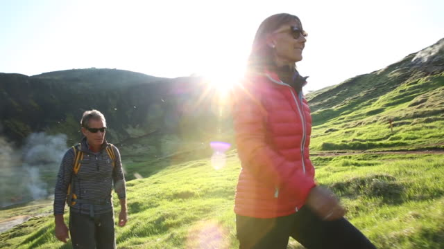 Man and woman hiking on a trail in a green field in Iceland