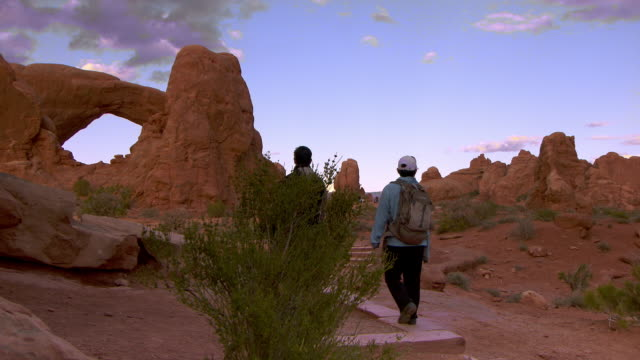 man and woman hiking on desert trail past camera towards south window arch in the spectacles area at sunset - gemeinsam gehen stock-videos und b-roll-filmmaterial
