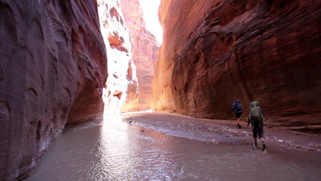 Man and woman hiking with backpacks  through river in deep red rock desert slot canyon.