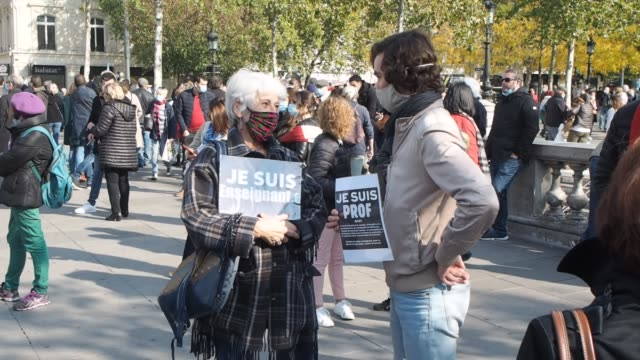 "man and woman hold signs saying ""je suis prof"" as people gather in place de la république to pay tribute to professor samuel paty and to defend... - decapitated stock videos & royalty-free footage"